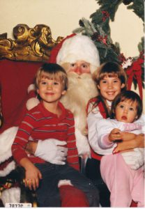 Me with my younger brother and cousin visiting Santa at Santaland, 1986