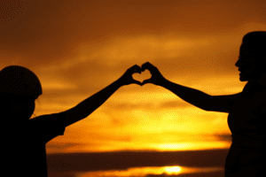 Silhouette of parent and child making heart shape with hands in front of sunset.