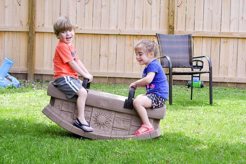 twin children, a boy and a girl, play on a seesaw