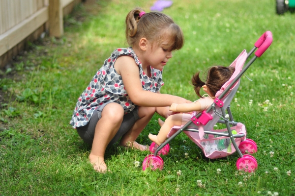 young girl outside, buckling a baby doll into a stroller