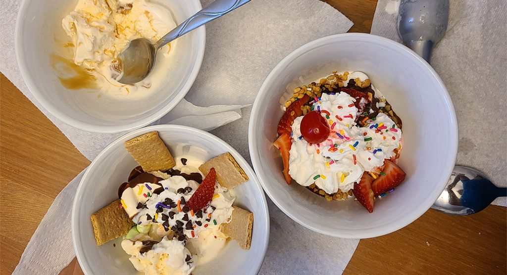three sundae bowls with vanilla ice cream and various toppings