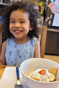 toddler bella smiling with her finished ice cream sundae